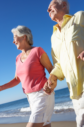 Senior Couple Running Along Beach Together